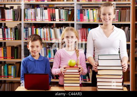Porträt der Schüler und Lehrer mit haufenweise Bücher in der Bibliothek