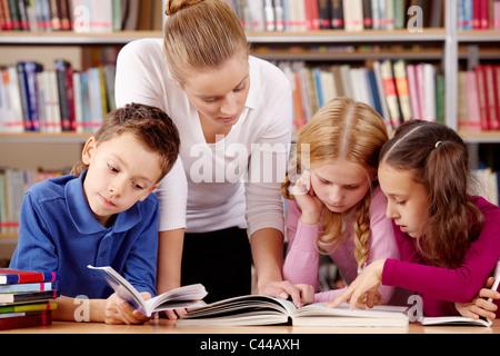 Porträt von Schülern und Lehrer lesen interessantes Buch in Bibliothek