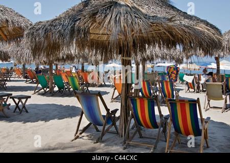 Stühle sind im Schatten Palapas und Sonnenschirme am Strand von Los Muertos Strand in Puerto Vallarta, Mexiko aufgereiht. - Stockfoto