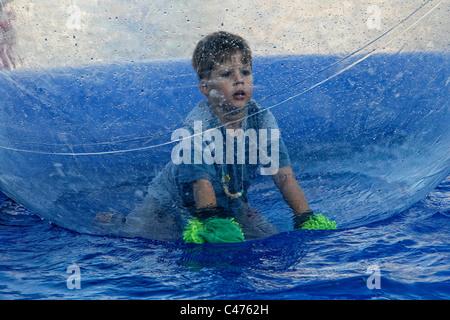 Ein deutscher aufgeregt 5-6 Jahre alter Junge kniend in einer riesigen aufblasbaren Blase auf dem Wasser - Stockfoto