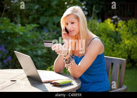 ... Junge Mädchen Sprechen über Moblie Telefon Online Shopping Mit  Kreditkarte Im Garten Auf Einem Wireless