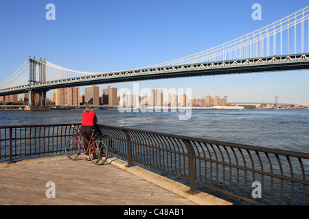 Eine Frau mit dem Fahrrad, Blick auf den East River, New York City, USA - Stockfoto
