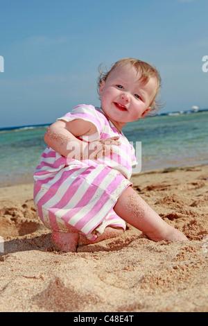 Model Release glückliches lächelndes Kind, ein einjähriges Mädchen spielen am Strand im Sommerurlaub - Stockfoto
