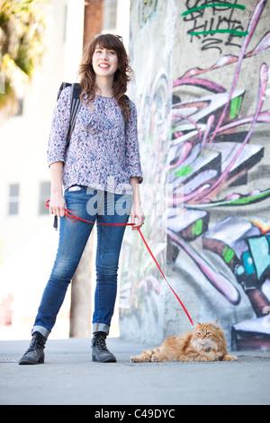 Eine lächelnde junge Frau mit einer langhaarigen orange Manx Katze an der Leine, stehend in einem städtischen Gebiet - Stockfoto
