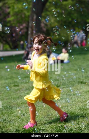 Eine Mädchen jagt Luftblasen während Entlein-Tages-Veranstaltung auf Boston Common, Boston, Massachusetts - Stockfoto