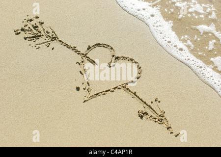 Herz durchbohrt von Amors Pfeil in den Sand gezeichnet - Stockfoto