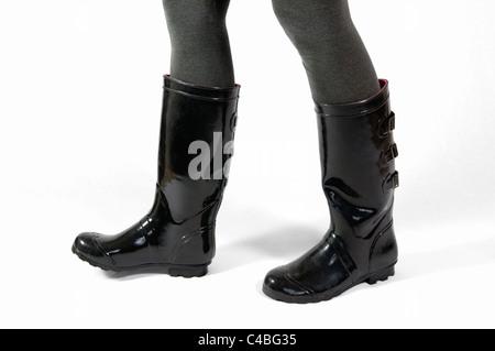 Unterhalb der Knie Schuss von ein paar Frauen Beine zu Fuß in schwarze Gummistiefel oder Wellington Stiefel gegen - Stockfoto