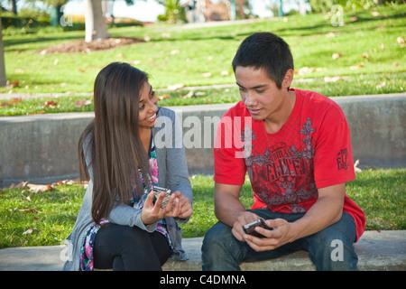 Junge und Mädchen sprechen iPhone Mobile Phones rassisch gemischten Mischung ethnischer Vielfalt vielfältige Teens - Stockfoto