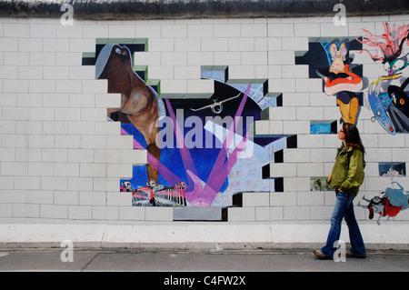 Ein Mädchen geht Vergangenheit malte das Album-Cover von Pink Floyd The Wall auf der Berliner Mauer an der East - Stockfoto