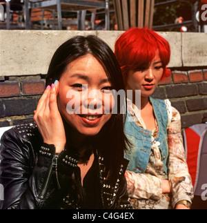 Junge asiatische Frauen sitzen vor der Anchor Pub in Central London England UK - Stockfoto