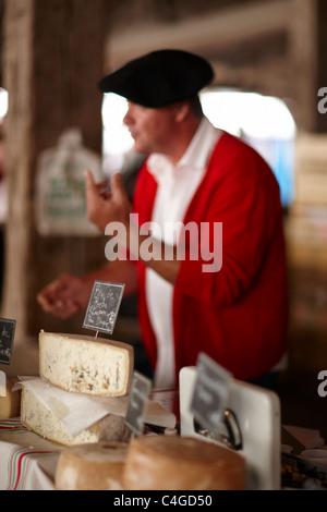 ein Mann verkauft Käse auf dem Markt in Revel, Languedoc, Midi-Pyrenäen, Frankreich - Stockfoto