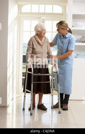 Pflegeperson hilft älteren Senior Frau mit Rollator - Stockfoto