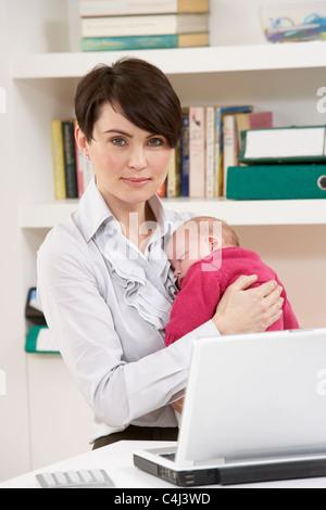 Frau mit Neugeborenen Arbeiten von zu Hause mit Laptop - Stockfoto