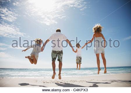 Familie Hand in Hand und springen am Strand - Stockfoto
