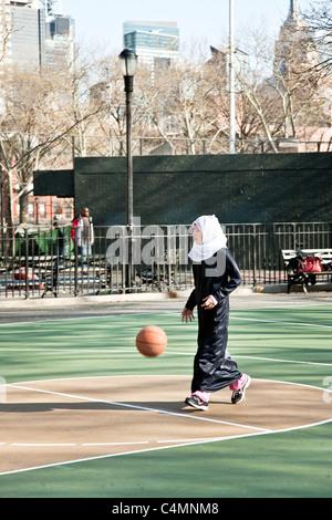 hübsche junges muslimische Mädchen im Kopftuch mit schwarzen Abaya über ihre Jeans spielt mit Fußball in New York City Spielplatz