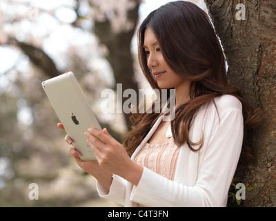 Junge Asiatin mit dem iPad in einem Park unter einem Kirschbaum - Stockfoto