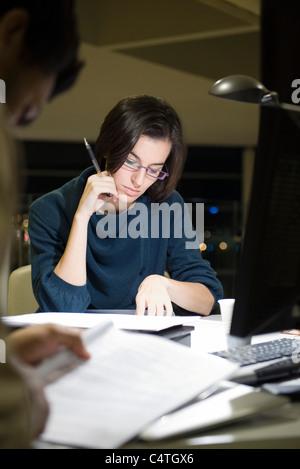 Kolleginnen und Kollegen lesen von Dokumenten im Büro in der Nacht - Stockfoto