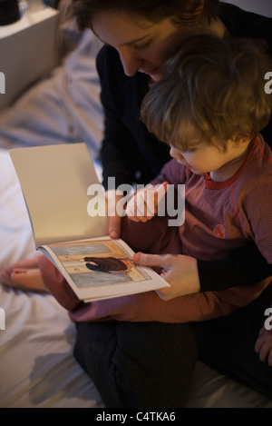 Mutter mit Kleinkind Sohn auf Schoß, gute-Nacht-Geschichte lesen - Stockfoto