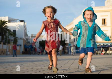 Junge Geschwister laufen hand in hand - Stockfoto