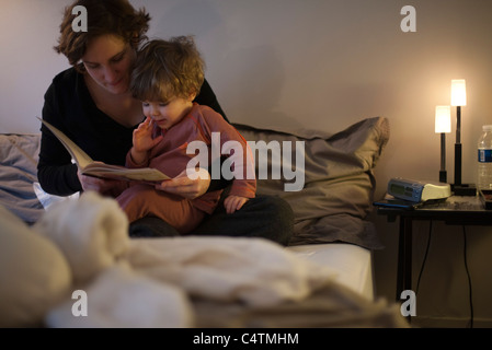 Mutter mit Kleinkind Sohn auf Schoß, Gutenachtgeschichte im Bett lesen - Stockfoto
