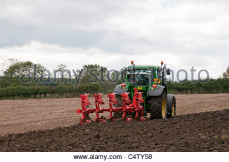 Green Farm Traktor arbeitet auf dem Feld, ziehen 5-Furchen reversible Pflug, Stoppelpflügen & Drehen Boden (Landwirt - Stockfoto