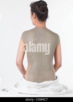 Frau mit Bentonit Lehm Körper wickeln Maske auf dem Rücken - Stockfoto