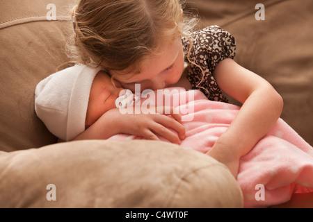 USA, Utah, Lehi, Mädchen (2-3) umfassende Babyschwester auf sofa - Stockfoto