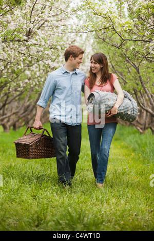 Young, Provo, Utah, USA paar mit Picknick-Korb im Obstgarten - Stockfoto