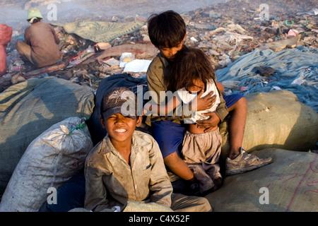 Ein junges Kind Arbeiter junge trägt einen Hut lächelt eine giftige und verschmutzten Müllhalde in Kambodscha. - Stockfoto