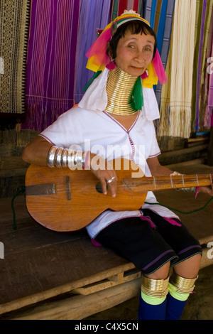 Karen Paduang Flüchtling Frau gold Ringe um den Hals tragen ist eine hölzerne Gitarrenspiel in einem Flüchtlingslager in Thailand. Stockfoto