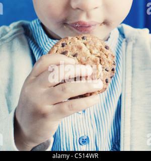 Kleines Mädchen hält Cookie, Mittelteil - Stockfoto