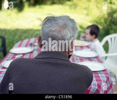 Ältere Mann sitzt am Tisch im Freien, Betrachtung Enkelkind - Stockfoto