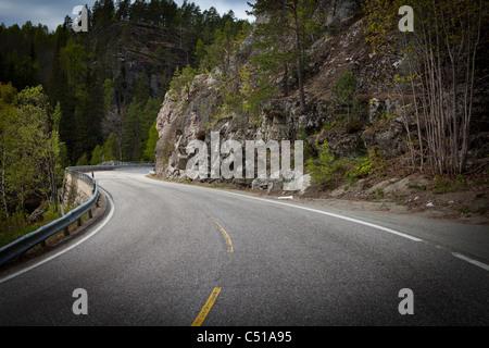 Klippenstraße Kurven rund um den Berg mit Bäumen wachsen auf steilen Felswänden - Stockfoto