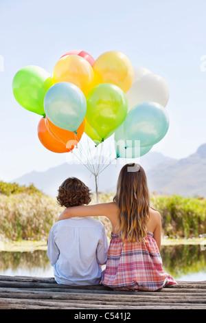 Rückansicht der Geschwister spielen mit Luftballons am pier - Stockfoto