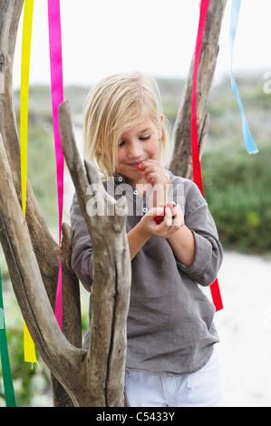 Mädchen an einen Baum gelehnt und Verzehr von Obst - Stockfoto