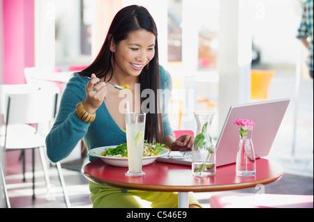 Schöne Frau, die beim Betrachten der Laptop in einem Restaurant Essen - Stockfoto