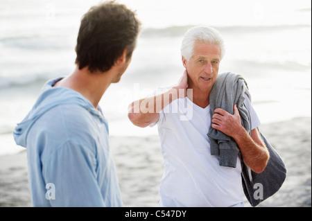 Ältere Mann im Gespräch mit seinem Sohn am Strand - Stockfoto