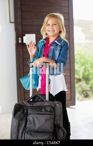 Mädchen mit Gepäck an der Tür ihre Hand winken - Stockfoto