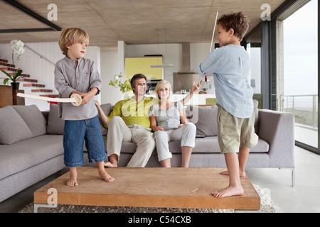 Jungen spielen mit ihren Eltern auf einer Couch sitzend - Stockfoto