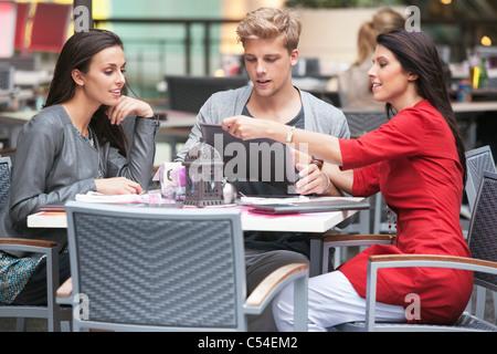 Junger Mann mit zwei jungen Frauen Blick auf die Speisekarte in einem restaurant - Stockfoto