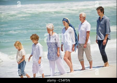 Multi-Generationen-Familie zu Fuß in einer Linie am Strand - Stockfoto