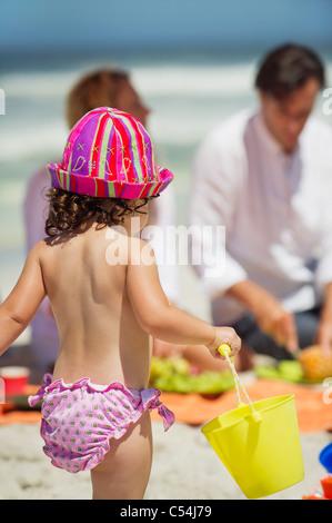 Rückansicht eines Mädchens mit einem Eimer am Strand - Stockfoto