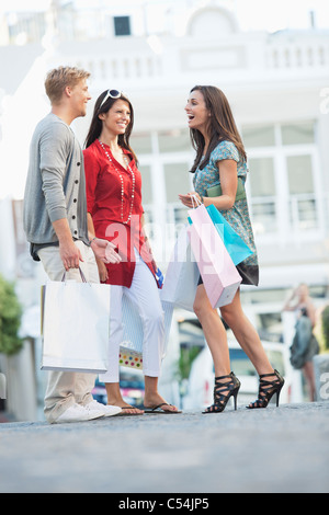 Junger Mann mit zwei Frauen halten Einkaufstaschen auf einer Straße
