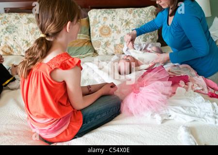 Mädchen Mitarbeitende Mutter putzt sich Babymädchen auf Bett - Stockfoto