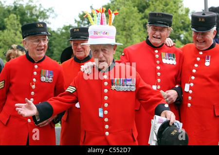 Männer in roten Uniformen feiern einen Geburtstag von einer von ihnen, Ascot, Großbritannien - Stockfoto