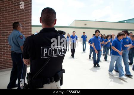 Polizist am Gymnasium in Pharr, Texas, überwacht die Studenten zu Fuß durch den Innenhof zwischen den Klassen - Stockfoto