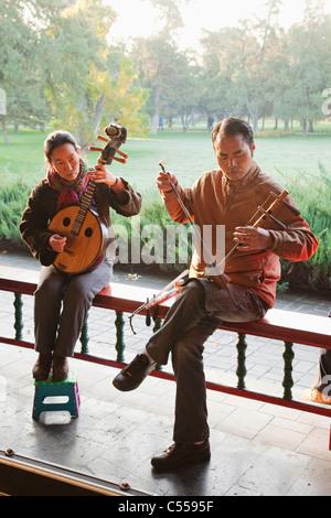 Mann mit einer Frau spielen traditionelle chinesische Streichinstrumente, Himmelstempel, Peking, China - Stockfoto