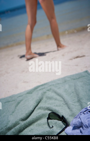 Handtuch am Strand mit Frau zu Fuß im Hintergrund - Stockfoto