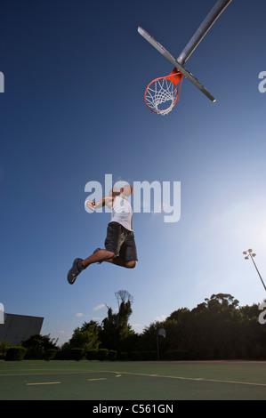 männliche machen Slam Dunk bei Outdoor-Basketball-Spiel - Stockfoto