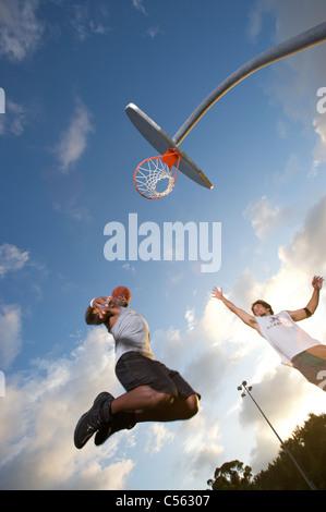 Männlich, scoring während der Outdoor-Basketball-Spiel, aufwärts Winkel in Richtung Ziel - Stockfoto